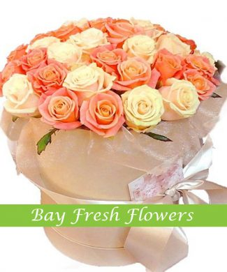orange and cream roses in a hat box