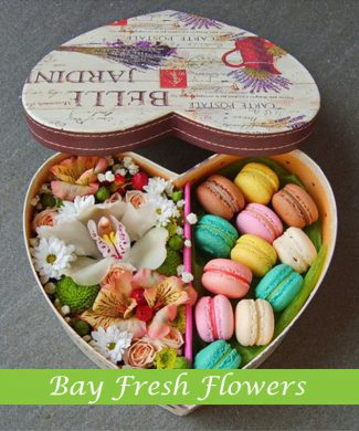 macaroons and flowers in a heart shape box