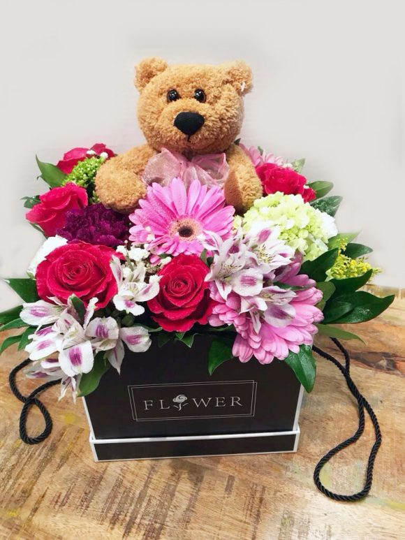 Flowers in a box with a toy